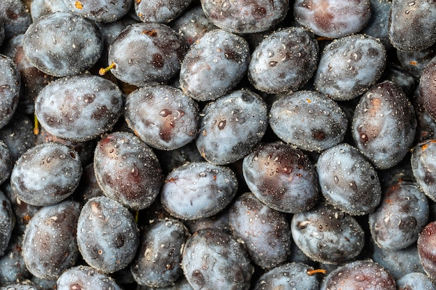 Un sacco di frutta fresca di prugne blu con gocce d'acqua