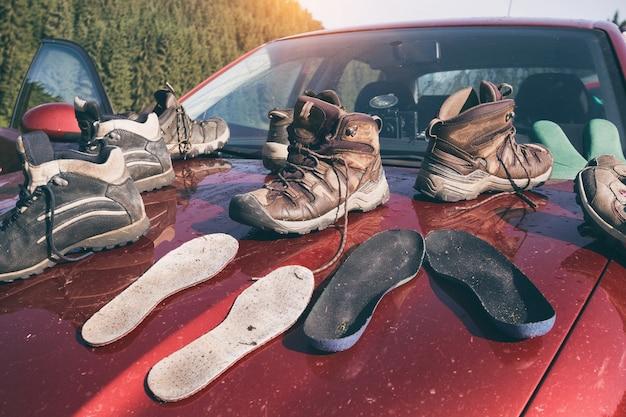 Un sacco di scarponi da trekking si trovano sul tetto dell'auto dopo il monitoraggio e il bellissimo paesaggio di montagna