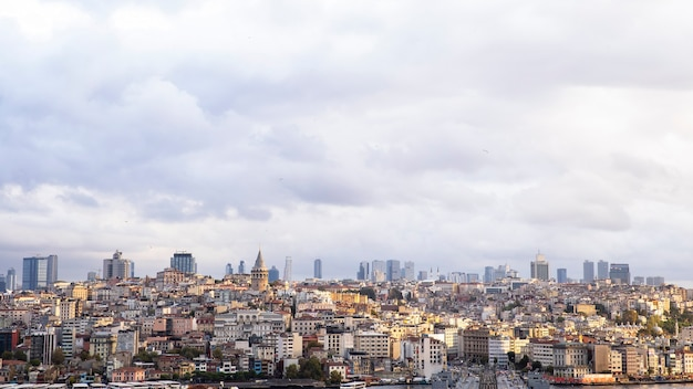 Un sacco di bassi edifici residenziali e alti moderni in lontananza, torre di galata a tempo nuvoloso istanbul, turchia