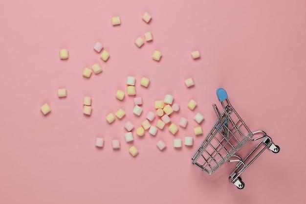Lotto di mini marshmallow e carrello della spesa su sfondo rosa. tendenza colore pastello. vista dall'alto