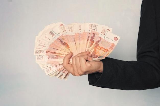 Un sacco di soldi nelle mani di un giovane uomo d'affari su sfondo blu. una pila di banconote di rubli russi con un valore nominale di 5000 rubli. uomo d'affari di successo