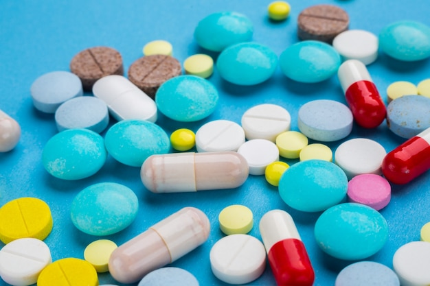Molte pillole multicolori su sfondo blu come concetto di trattamento medico