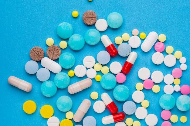 Molte pillole multicolori su sfondo blu un concetto di trattamento medico con prescrizione