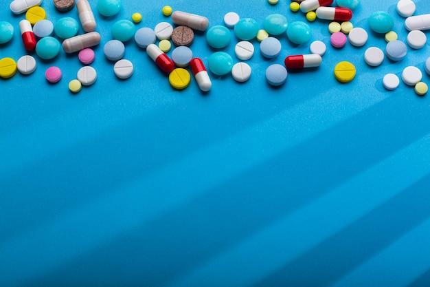 Molte pillole multicolori su sfondo blu con spazio libero per il testo