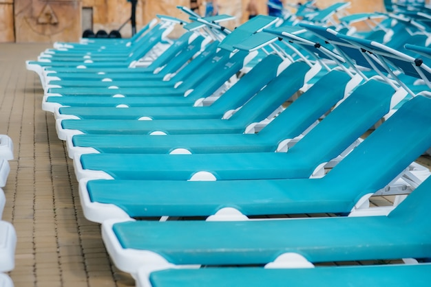 Un sacco di nuovi bellissimi lettini blu sono in piedi vicino alla piscina dell'hotel in una giornata di sole. buone vacanze. vacanze estive e turismo.
