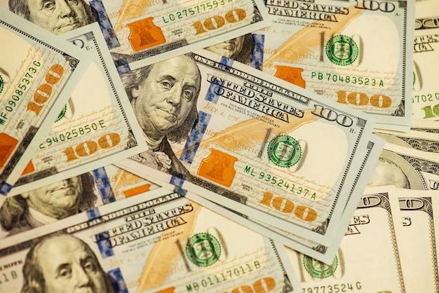 Lotto di sfondo primo piano banconote da cento dollari. molti dollari