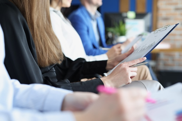 Molte persone con documenti in mano sono sedute in primo piano sulla formazione aziendale