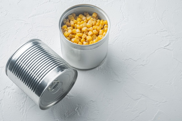 Un sacco di pezzi di mais giallo in scatola in lattina di metallo, su sfondo bianco con spazio di copia per il testo