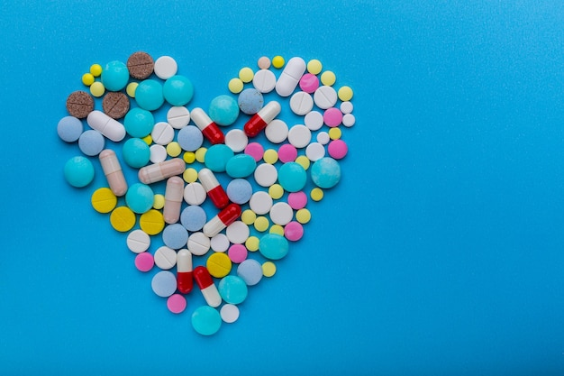 Molte pillole a forma di cuore su sfondo blu come simbolo di trattamento per proteggere il cuore