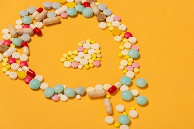 Molte pillole su sfondo arancione a forma di cuore come simbolo di cure mediche per un cuore sano. aiuto di emergenza in caso di infarto.