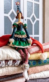 Un sacco di maglioni e pullover di diversi colori piegati in due pile e bambola giocattolo fatta a mano.