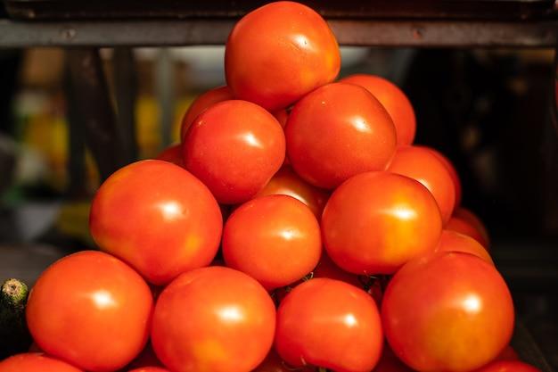 Molti pomodori giacciono uno sopra l'altro a forma di piramide alla luce del sole