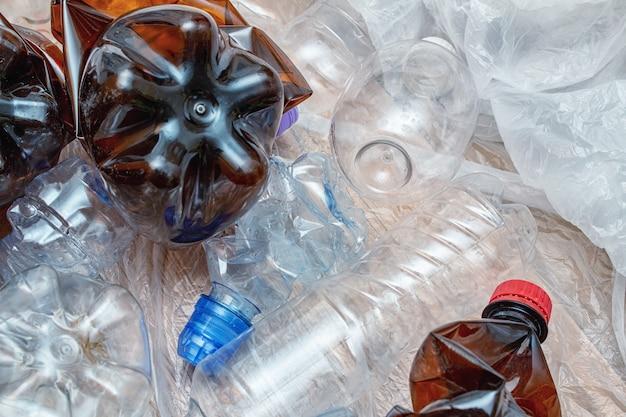 Lotto di plastica, bottiglie, pacchetti usati. inquinamento, riciclo, sfondo eco.