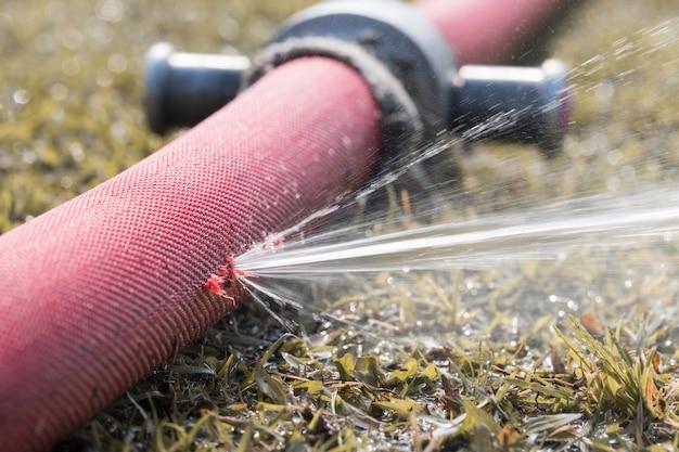 Molta acqua che fuoriesce dal foro di un tubo rosso in giardino