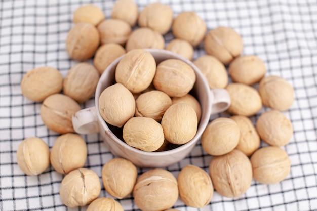 Molte noci intere in una tazza su un primo piano del tovagliolo. alimento sano, biologico e salutare con un alto contenuto di proteine e proteine.