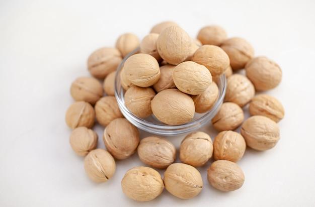 Un sacco di noci intere in una tazza su un primo piano sfondo bianco. alimento sano e biologico con un alto contenuto di proteine e proteine.