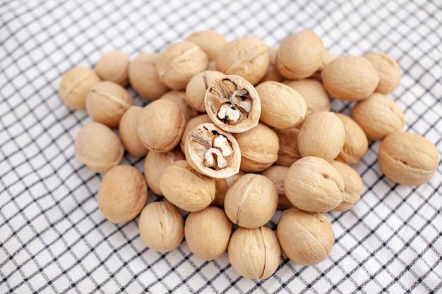 Molte noci intere su un primo piano del tovagliolo. alimento sano, biologico e salutare con un alto contenuto di proteine e proteine.