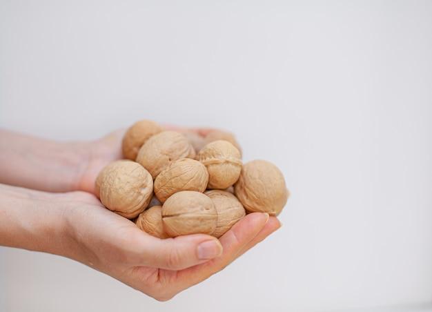 Un sacco di noci intere nelle mani delle donne su un primo piano sfondo bianco. alimento sano e biologico con un alto contenuto di proteine e proteine.