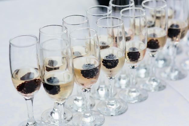 Molti bicchieri di vino con un delizioso champagne fresco o vino bianco al catering dell'evento