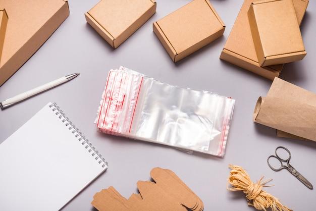 Lotto di sacchetti con chiusura a zip e scatole di cartone marrone su superficie grigia