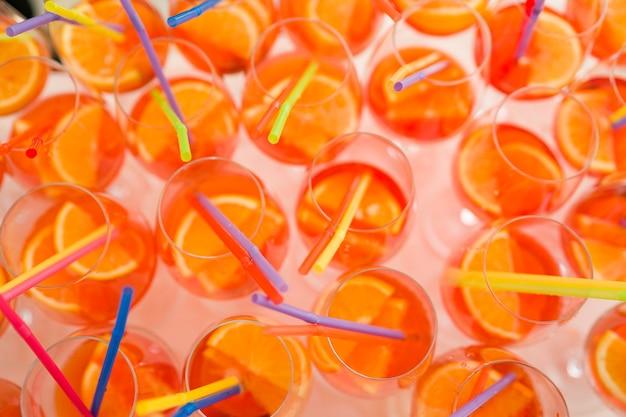 Tanti bicchieri da cocktail aperol spritz con tubi di plastica