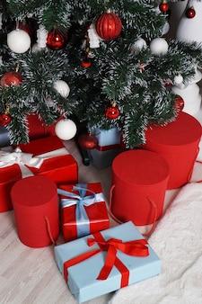 Un sacco di bei regali di natale avvolti in scatole rotonde in rosso e blu sotto l'albero di natale.