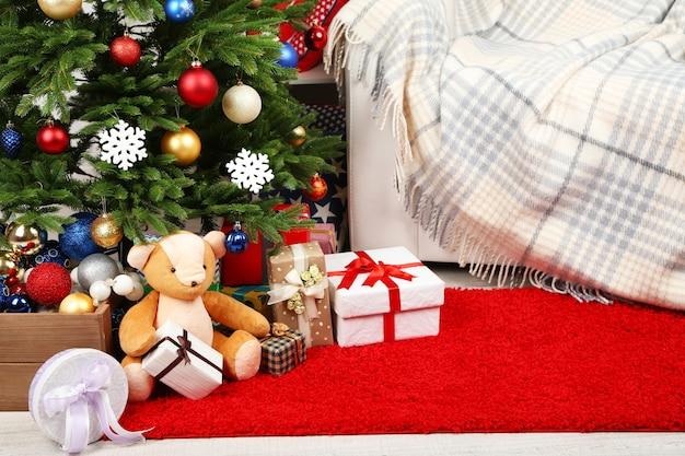 Un sacco di regali di natale sul pavimento in interni festivi
