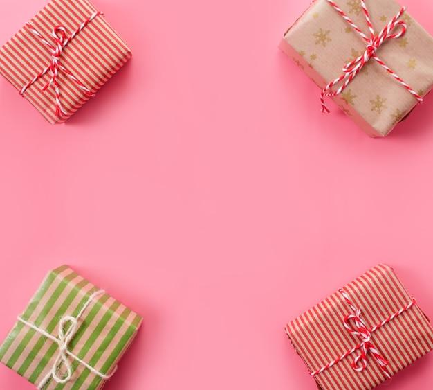 Un sacco di regali di natale su sfondo rosa.