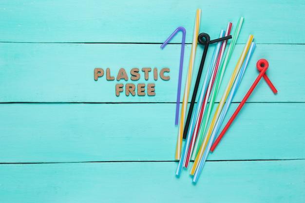 Un sacco di tubi da cocktail su una superficie di legno blu con testo in plastica gratis