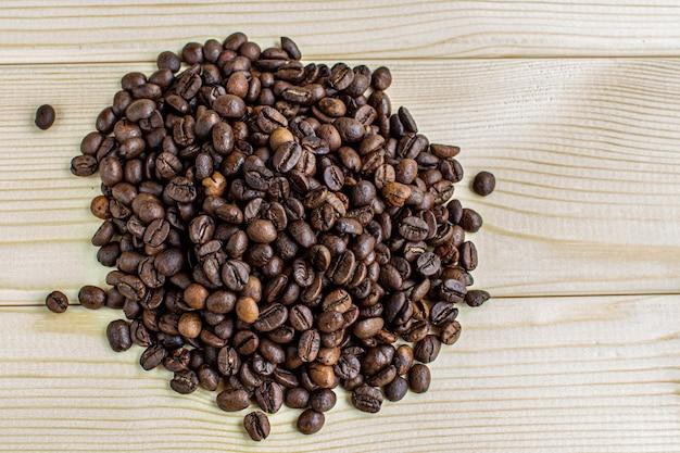 Un sacco di chicchi di caffè su uno sfondo di legno. c'è un posto per l'inserimento.