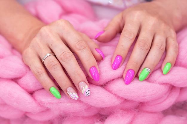Molte mani di manicure di colore lucido hanno diverse macchie su sfondo rosa