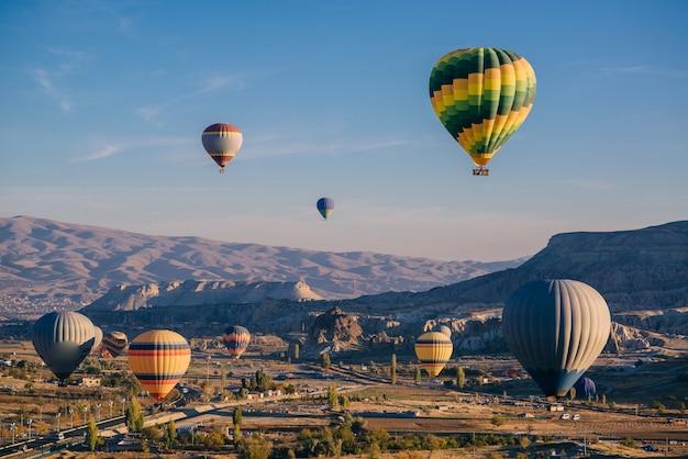 Tanti palloncini colorati nel cielo sopra le montagne