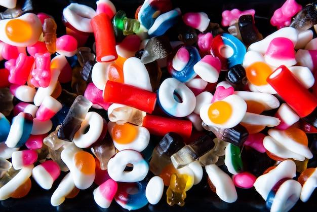 Un sacco di caramelle colorate, caramelle gommose, dolci e caramelle per un compleanno. festa di caramelle miste sfondo.