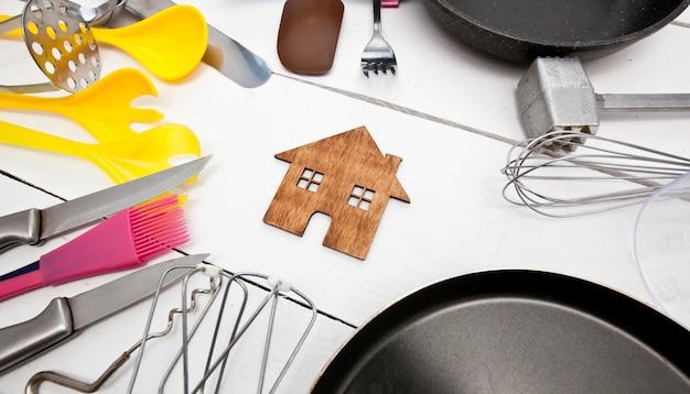 Un sacco di utensili da cucina diversi sul tavolo di legno e una casetta di legno tra di loro