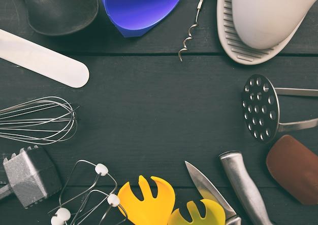 Un sacco di utensili da cucina diversi sul tavolo di legno