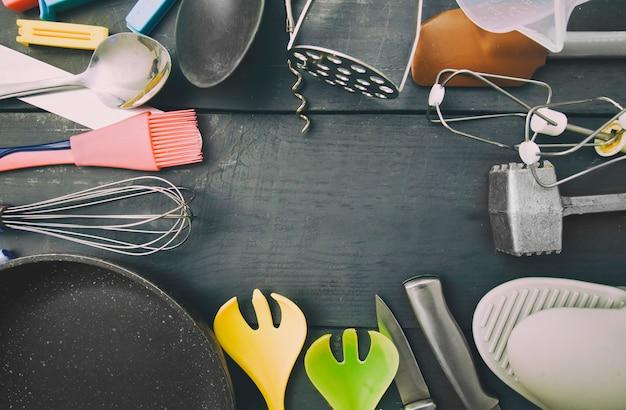 Molti utensili da cucina diversi sul tavolo di legno