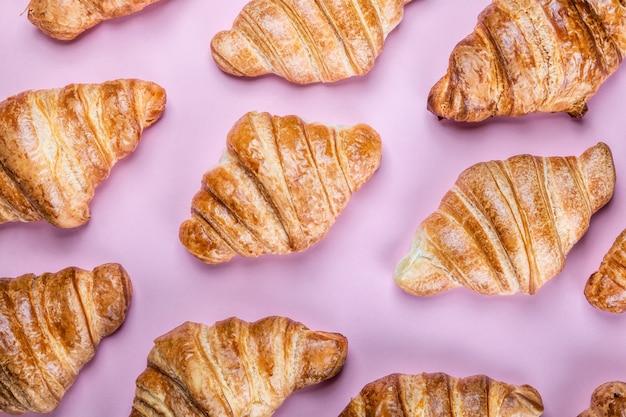 Tanti croissant appena sfornati su sfondo rosa. sfondo di croissant