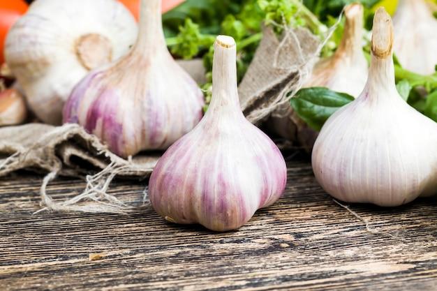 Un sacco di aglio sul tagliere durante la cottura, tavolo da cucina durante la cottura del cibo, primo piano
