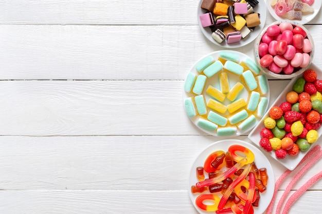 Un sacco di caramelle gommose e gelatina in un piatto su uno sfondo di legno bianco con spazio per le copie. vista dall'alto