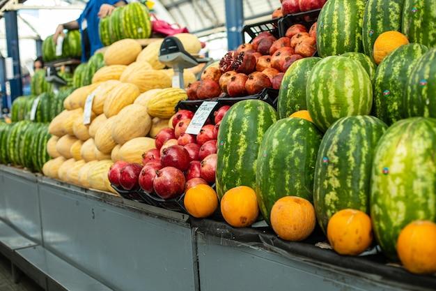 Un sacco di grandi cocomeri verdi in piedi accanto ad arance e altri frutti sullo scaffale del supermercato.