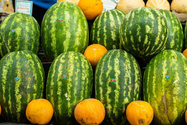 Un sacco di grandi cocomeri verdi in piedi accanto alle arance sullo scaffale del supermercato.