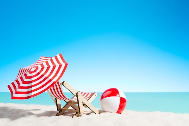 Sedia a sdraio con ombrellone e pallone da spiaggia sulla costa, cielo con copia spazio