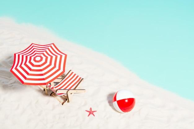 Sedia a sdraio con ombrellone e pallone da spiaggia sulla costa, vista dall'alto