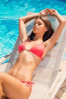 Oziare a bordo piscina. vista dall'alto di una bella giovane donna in bikini che si rilassa sulla sedia a sdraio a bordo piscina