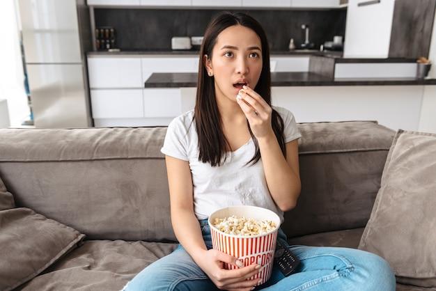 Adoro la donna asiatica che guarda la tv mentre è seduta su un divano e mangia popcorn a casa