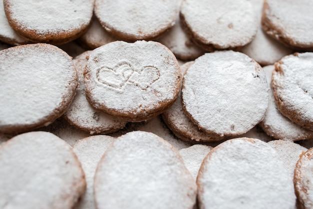 Righe di biscotti d'amore con stampa a forma di cuori con decorazione in polvere di zucchero