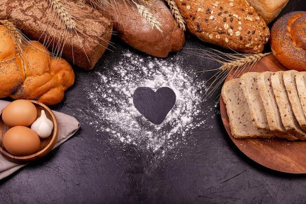 Amo cucinare. vari di pane di segale su uno sfondo scuro. copia spazio.