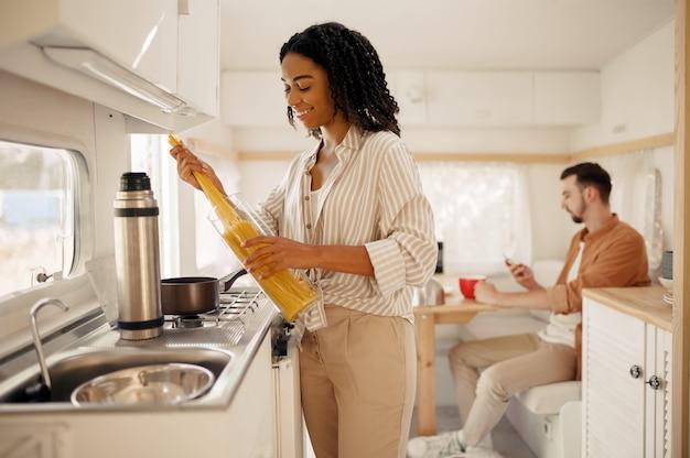 Amo le coppie che cucinano nella cucina del camper, in campeggio in un rimorchio. l'uomo e la donna viaggiano in furgone, romantiche vacanze in camper, gli svaghi dei campeggiatori in camper