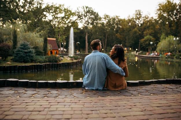 Amore coppia che abbraccia allo stagno nel parco estivo. l'uomo e la donna si rilassano all'aperto, prato verde. famiglia che abbraccia vicino al lago in estate, weekend nella natura