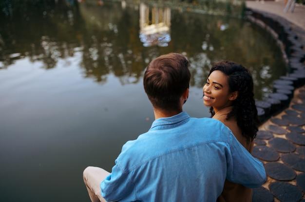 Amore coppia che abbraccia allo stagno nel parco estivo. l'uomo e la donna si rilassano all'aperto, prato verde. famiglia che abbraccia vicino al lago in estate, weekend all'aperto